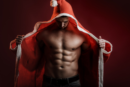 One sexual strong young new year man with muscular body in red and white christmas santa coat standing posing on studio background, horizontal picture Stock Photo