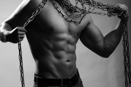 One handsome sexual strong young man with muscular body in blue jeans holding rope with hands hanging on neck and shoulders standing posing in studio black and white, horizontal picture Stock Photo