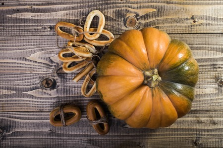 string top: Photo top distant view closeup rustic autumn still life big whole fresh orange pumpkin with bunches of hard oval cracknels bind with string on wooden table on timber background, horizontal picture