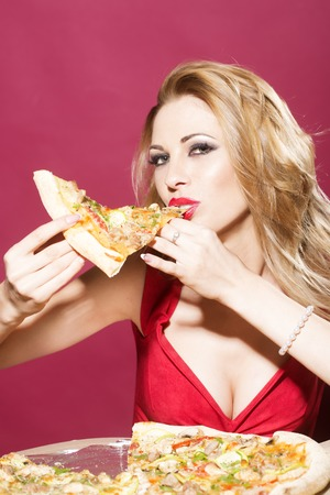 sexy food: Portrait of pretty sexy blond young woman with bright makeup looking straight wearing dress with deep decollete holding and eating piece of appetizing pizza on red background indoor, vertical photo