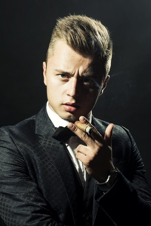 upper half: Portrait of presentable bold enchanting beautiful blonde boy in stylish formal suit and bow-tie holding cigar looking straight studio on black background closeup, vertical picture