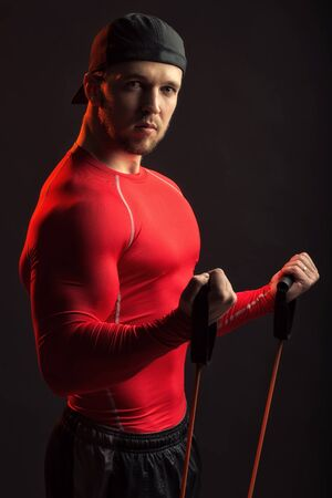 training device: One sexual strong young man with muscular body in red sport shirt and black cap holding training device standing on studio background, vertical picture