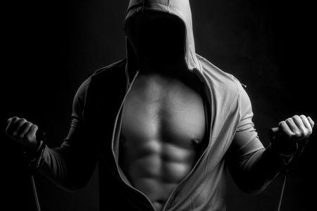 training device: One sexual strong young man with muscular body in grey sport jacket with hood holding training device standing in studio black and white, horizontal picture Stock Photo