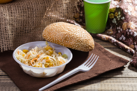 sesame seed bun: Country still life with fresh baked sesame seed bun vegetable salad with disposable green cup and white fork lying on brown brat on rustic wooden background, horizontal picture