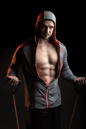 muscular body: One sexual strong young man with muscular body in grey sport jacket with hood holding training device standing on studio black background, vertical picture