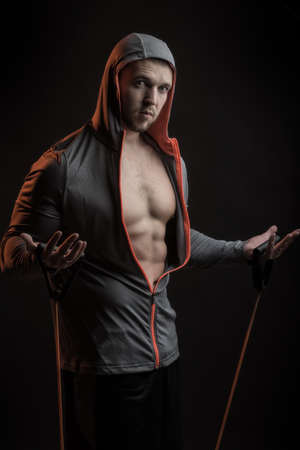 sexual anatomy: One sexual strong young man with muscular body in grey sport jacket with hood holding training device standing on studio black background, vertical picture