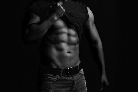 Één knappe seksuele sterke jonge mens met spierlichaam in jeans met overhemd op schouder het bevindende stellen op studio achtergrond zwart-wit, horizontaal beeld