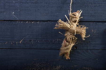 cross linked: Photo closeup folk crafts one cross shaped Halloween rag voodoo doll made of sackcloth pierced with sticks on chest decoration hanging on rope over blue timber background, horizontal picture Stock Photo