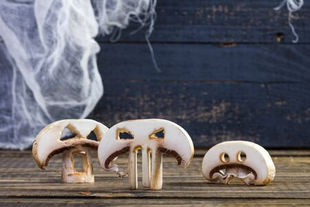 button mushrooms: Photo closeup still life three slices of white button mushrooms champignons with cut Halloween ghost faces eyes standing on wooden table on blue rustic timber background, horizontal picture