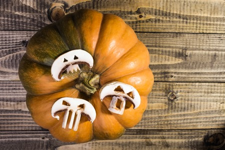 button mushrooms: Top view rotary photo still life one big whole fresh orange pumpkin with three slices of white button mushrooms with cut Halloween ghost faces on wooden table on timber background, horizontal picture Stock Photo