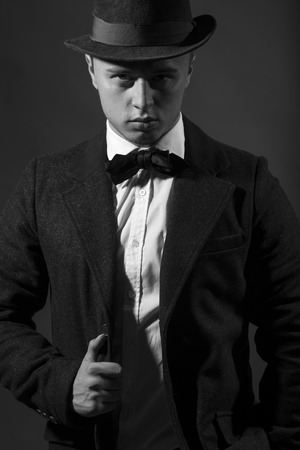 upper half: Portrait of retro fashion fifties young attractive confident contemptuous man looking straight dressed in formal suit with bow-tie and hat studio on dark background black and white, vertical