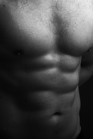 nackte brust: Closeup view of one handsome sexual strong young male bare chest of muscular wet body standing posing on studio background black and white, vertical picture
