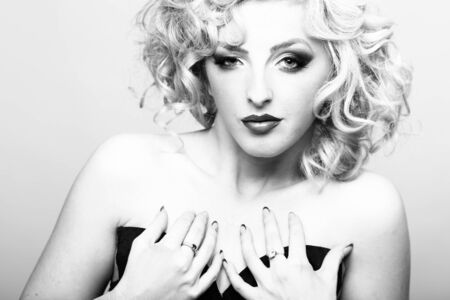 nude young woman: Portrait of one beautiful sensual sexy young retro blonde woman with curly hair and bright makeup looking forward holding hands on chest in studio black and white, horizontal picture Stock Photo