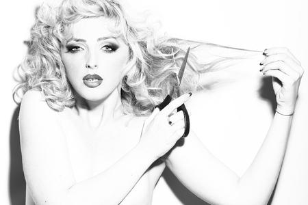 Portret van één mooie sensuele sexy jonge retro blondevrouw met krullend haar en heldere make-up die voorwaartse holdingsschaar kijken in studio zwart-wit, horizontaal beeld