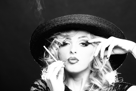 nude girl young: Portrait of one beautiful sensual sexy young retro blonde woman with curly hair and bright makeup in round hat looking forward smoking cigarette on studio background, horizontal picture
