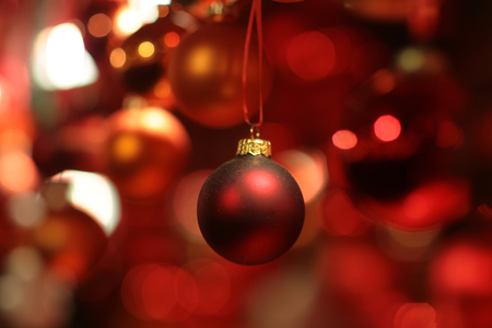 Picture of shiny and blurred red Christmas garland made from baubles of different sizes texture and shades, horizontal picture