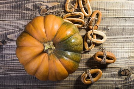 hard bound: Photo top distant view closeup rustic autumn still life big whole fresh orange pumpkin with bunches of hard oval cracknels bind with string on wooden table on timber background, horizontal picture