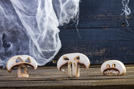 Photo still life three slices of white button mushrooms champignons with cut Halloween ghost faces eyes standing on wooden table on blue rustic timber background, horizontal picture