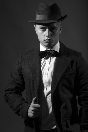 upper half: Handsome imposing assured proud enchanting young man wearing elegant suit with bow-tie and hat in retro fifties fashion looking straight studio on dark background black and white, vertical picture