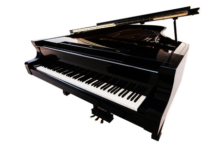 Closeup view of one beautiful big shiny black open piano forte with white key board standing in studio isolated on white background, horizontal picture Foto de archivo