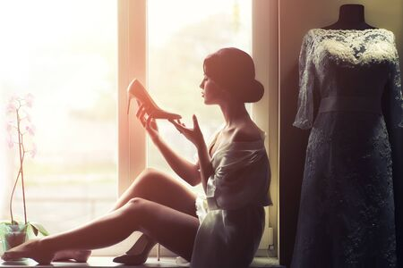 nude brunette: Silhouette of one young beautiful slim brunette woman in underwear sitting and drinking coffee in morning looking at window near white wedding lace dress on mannequin, horizontal picture