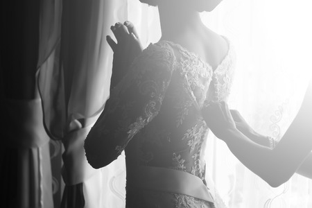 nude bride: Silhouette of one young slim bride dressing with help of female hands in lace wedding dress preparating for ceremony standing near window black and white, horizontal picture Stock Photo