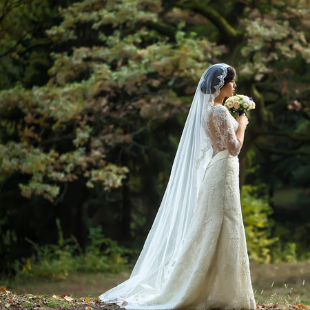 Full length side view of one beautiful sensual young brunette bride in long white wedding dress and veil standing in forest holding bouquet outdoor on natural background, square picture