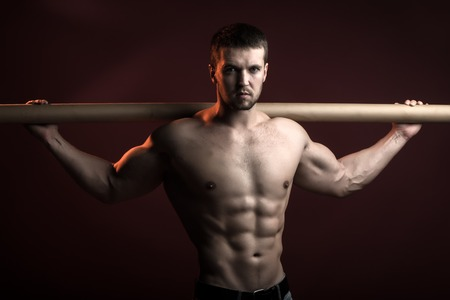 man power: One sexual strong young man with muscular body in jeans holding iron crossbar standing posing in studio on red background, horizontal picture Stock Photo