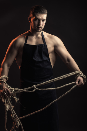 pectoral muscle: One handsome sexual strong young man with muscular body in working blue apron holding rope standing posing in studio on black background, vertical picture