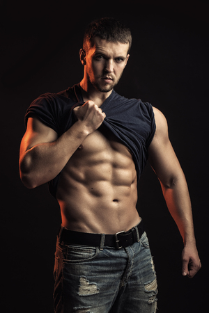 One handsome sexual strong young man with muscular body in blue jeans with shirt on shoulder standing posing in studio on black background, vertical picture Stock Photo