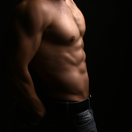 sexual anatomy: Closeup view of one handsome sexual strong young male bare chest of muscular body standing posing on studio background, square picture Stock Photo