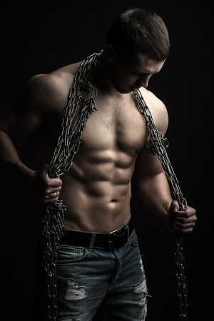 muscular body: One handsome sexual strong young man with muscular body in blue jeans holding rope with hands hanging on neck and shoulders standing posing in studio on black background, vertical picture Stock Photo