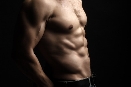 nackte brust: Closeup view of one handsome sexual strong young male bare chest of muscular body standing posing on studio background, horizontal picture