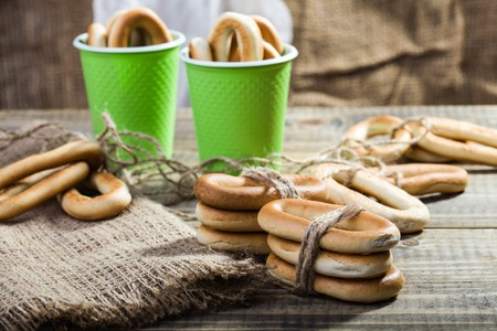 heaped: Still life mass of hard oval cracknels bind with string in bunches lying on sackcloth wooden table and peeking out of two disposable green cups heaped high on rustic background, horizontal picture