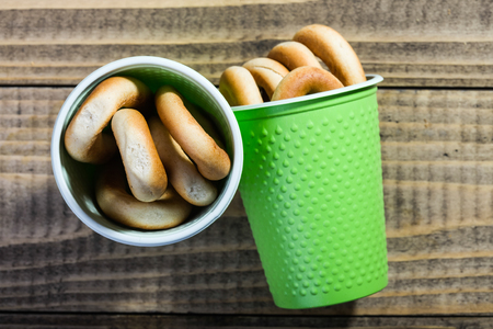heaped: Photo top view of two disposable green cups containing hard oval cracknels heaped high standing and fallen on timber background, horizontal picture