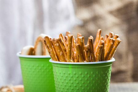 peaking: Photo still life closeup of two disposable green cups containing stick biscuits straws peaking out and hard oval cracknels heaped high standing on blurred rustic background, horizontal picture