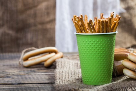 heaped: Still life one disposable green cup containing straws and groups of hard oval cracknels bind with string in bunches lying on sackcloth wooden table on blurred rustic background, horizontal picture Stock Photo