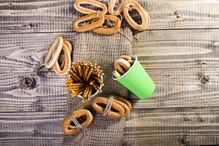 peaking: Photo top view disposable two green cups containing straws hard oval cracknels peaking out and bunches bind with string lying on sackcloth wooden table on timber background, horizontal picture