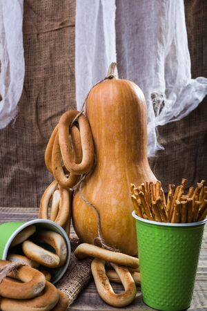 bind: Still life big gourd with bunches bind with string lying on sackcloth two disposable green cups with straws and hard oval cracknels standing on wooden table on rustic background, vertical picture Stock Photo