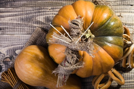 string top: Photo top view still life voodoo doll with sticks on chest lying on one orange pumpkin gourd bunches of hard oval cracknels bind with string on wooden table on timber background, horizontal picture