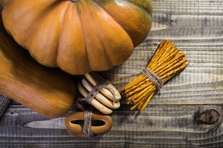 string together: Photo top view still life sheaf of delicious straws hard cracknels tied together with string and partial big whole fresh orange pumpkin gourd on wooden table on timber background, horizontal picture Stock Photo