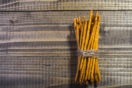 string together: Photo top view bread and flour products one sheaf of delicious stick biscuits straws tied together with string laying on wooden table on timber background, horizontal picture