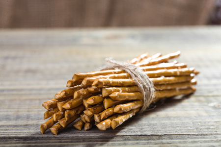 string together: Photo closeup bread and flour products one sheaf of delicious stick biscuits straws tied together with string laying on wooden table on blurred timber background, horizontal picture