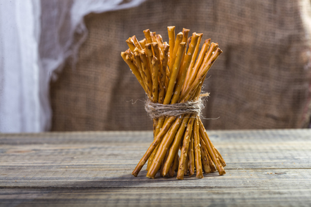 string together: Photo of bread and flour products one sheaf of delicious stick biscuits straws tied together with string standing on wooden table on blurred rustic background, horizontal picture