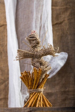 string together: Photo still life closeup one sheaf of delicious stick biscuits straws tied together with string voodoo doll with sticks on chest on wooden table on blurred rustic background, vertical picture Stock Photo