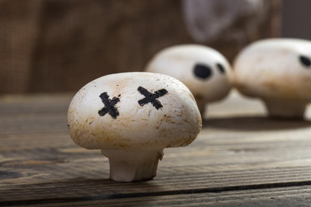 ghost face: Photo closeup still life of one Halloween white champignon with ghost face eyes drawn in black felt pen standing on wooden table on blurred group of button mushrooms background, horizontal picture Stock Photo