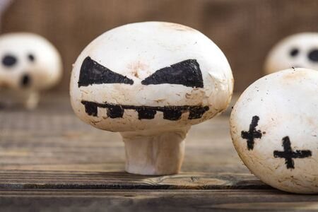 felt: Photo closeup still life some Halloween white champignons with ghost face smile drawn in black felt pen standing on wooden table on blurred group of button mushrooms background, horizontal picture