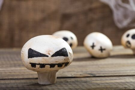 ghost face: Photo closeup still life of one Halloween white champignon with ghost face smile drawn in black felt pen standing on wooden table on blurred group of button mushrooms background, horizontal picture