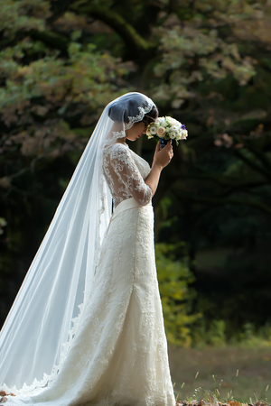 Full length side view of one beautiful sensual young brunette bride in long white wedding dress and veil standing in forest holding bouquet outdoor on natural background, vertical picture Stock Photo