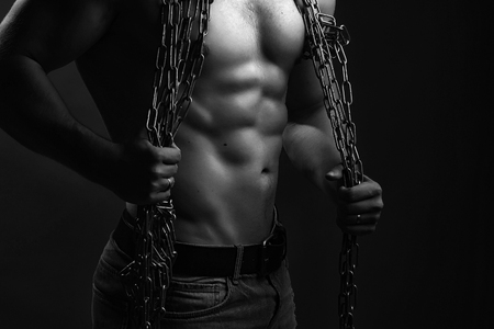 sexual anatomy: One handsome sexual strong young man with muscular body in blue jeans holding rope with hands hanging on neck and shoulders standing posing in studio black and white, horizontal picture Stock Photo